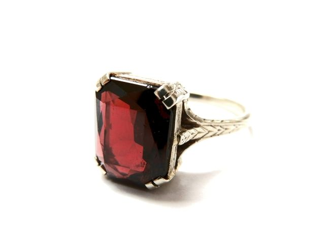 A Garnet Solitaire Ring, exquisitly engraved on shoulders and shank