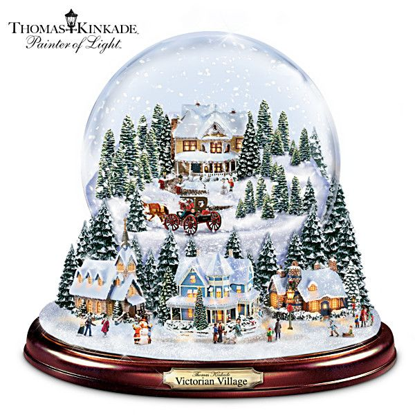 "Thomas Kinkade Victorian Village Snowglobe Limited edition. A first-ever illuminated glass snowglobe with swirling snow, two handcrafted sculptural scenes inside and out. Plays 8 holiday songs. Measures 7"" H"