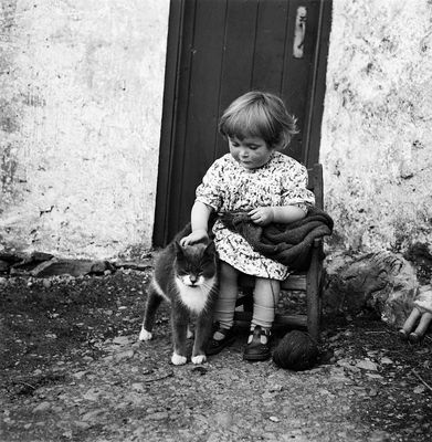 Girl with cat: Chrissie Cheyne seated with knitting, petting a cat. She wears a knitting belt.