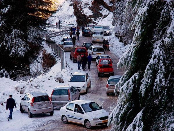 Vehices move slowly on a snow covered road at Kufri near Shimla.