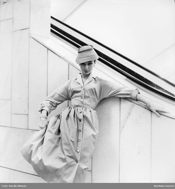 Konfektion, 1955. Modell i ljus klänning, handskar och hatt vid rulltrappa på Nordiska Kompaniet. Foto: Nordin Nilsson