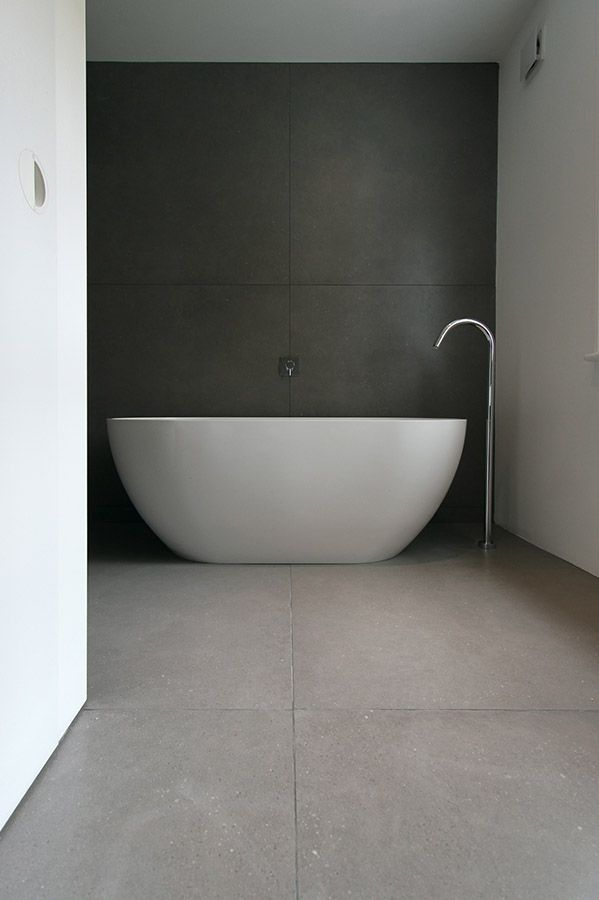 minimalist bathroom oversized tub with dark wall provides the perfect contrast by