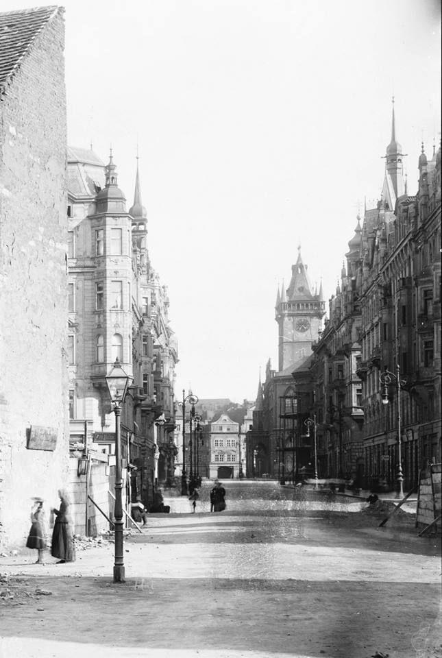 Průhled Pařížskou, 1904. Bourání započalo roku 1896 v místech ústí hlavní třídy nové čtvrti do Staroměstského náměstí. Trasa nové ulice nerespektovala původní uliční síť a byla v podstatě průlomem do historického půdorysu. Po obou stranách takto vzniklé Mikulášské ulice pak kupodivu nová zástavba zachovává průběh původních ulic, i když ve vyrovnaných liniích. Během prvních tří let byly zbořeny ulice jižně od Široké a přes protesty i zástavba domů severní strany Staroměstského náměstí.