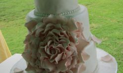 three tier wedding cake with large pink center sugar paste flower, wedding on oahu, oceanfront venue, wedding by hawaii weddings by tori roger, photo by rachel robertson