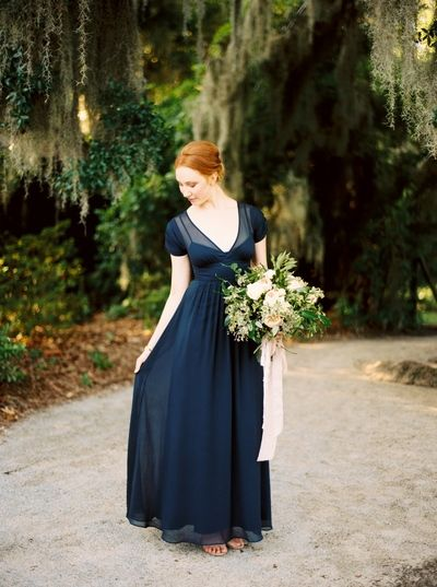 midnight blue brides dress with peach and green bouquet
