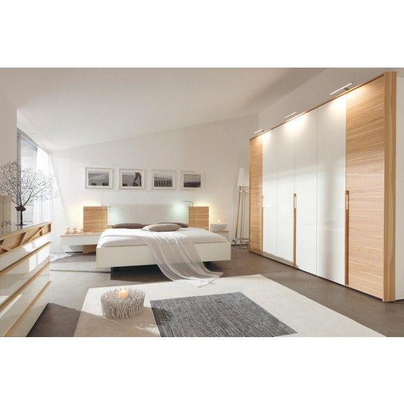 """Das Schlafzimmer """"Cutaro"""" von HÜLSTA lässt keine Wünsche offen. Die stimmige Kombination besteht aus einem Bett, einem geräumigen Kleiderschrank und 2 Nachtkästchen. Alle Möbel sind in elegantem Weiß und Eschefarben gehalten. Auf dem bequemen Bett mit einer Liegefläche von ca. 180 x 200 cm (B x L) können Sie sich mit Ihrem Partner entspannen. Auf den praktischen Nachtkästchen können Sie dabei Brille, Ladegeräte oder die neue Lieblingslektüre ablegen."""