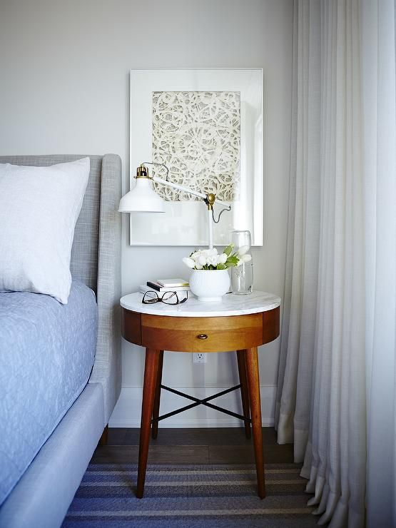 Restful white, gray, and blue bedroom boasts a heather gray wingback bed covered in white and blue bedding and positioned beside a West Elm Penelope Nightstand illuminated by a white swing arm table lamp placed in front of a white framed art piece beside a windows dressed in white curtains.