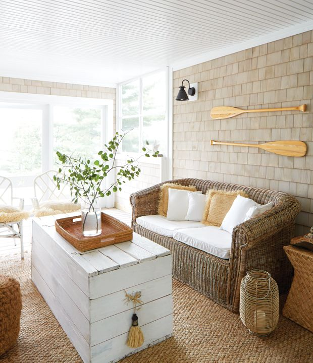 Screened-in porch with wicker seating and woven accents for a breezy feel. A white-painted wood crate serves as a casual coffee table would be an easy DIY.