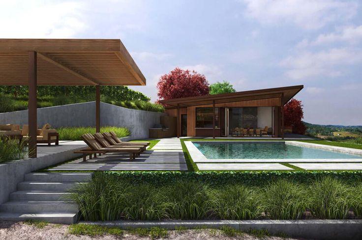 La terrasse devant la maison est aménagée de transats autour d'une grande piscine extérieure