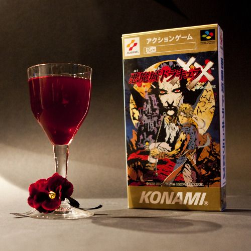"""Vampire's Kiss (Castlevania cocktail)    Ingredients: ½ Red Wine (or Port wine if you prefer it sweeter) ½ Passoa (Passion fruit liqueur) Directions: Stir the ingredients together and pour into a small wine glass. Drink and only smash your glass on the floor if you don't mind losing a glass.    """"What is a man? A miserable little pile of secrets! But enough talk… Have at you!"""" -Dracula (Castlevania: Symphony of the Night)    Drink created and photographed by Heidi from Retro-video-gaming.com."""