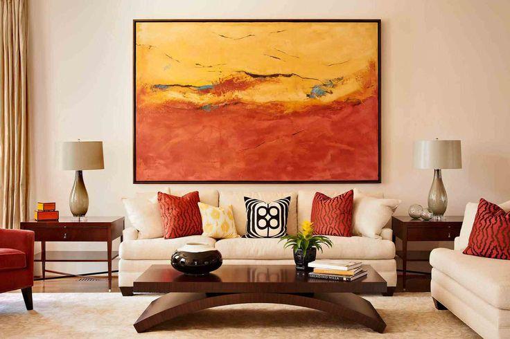 Feng Shui salon : tableau abstrait en tons chaleureux, canapé droit en blanc cassé, table basse en bois et coussins décoratifs