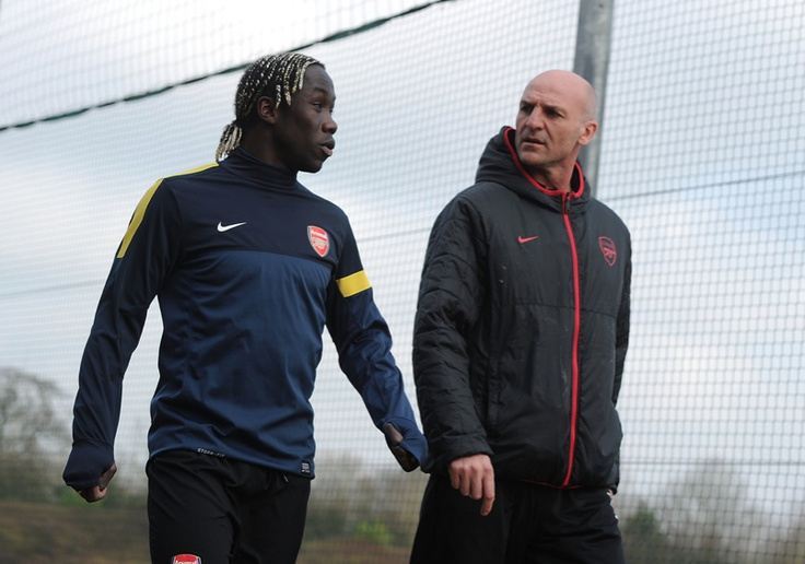 Bacary Sagna and Steve Bould before a training session ahead of their UEFA Champions League match against FC Bayern Muenchen at London Colney (February 2013) by Stuart MacFarlane