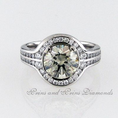 The centre stone is a 2.417ct M/SI2 round brilliant cut diamond with 50 = 0.43ct round diamonds channel set in an 18k white gold ring