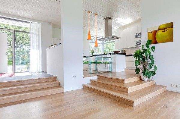 The elevated kitchen floats above the dining room in an open plan layout allowing light and air to flow throughout the space.