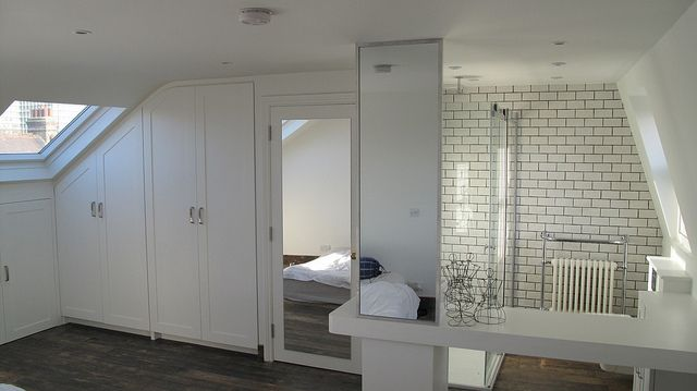 Loft Bedroom into open bathroom.  Dark floor works well with the white tiles and units.