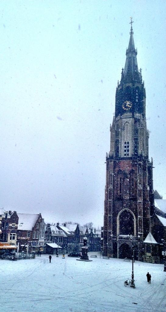 Standbeeld van Hugo de Groot en de Nieuwe Kerk op de besneeuwde Markt in Delft