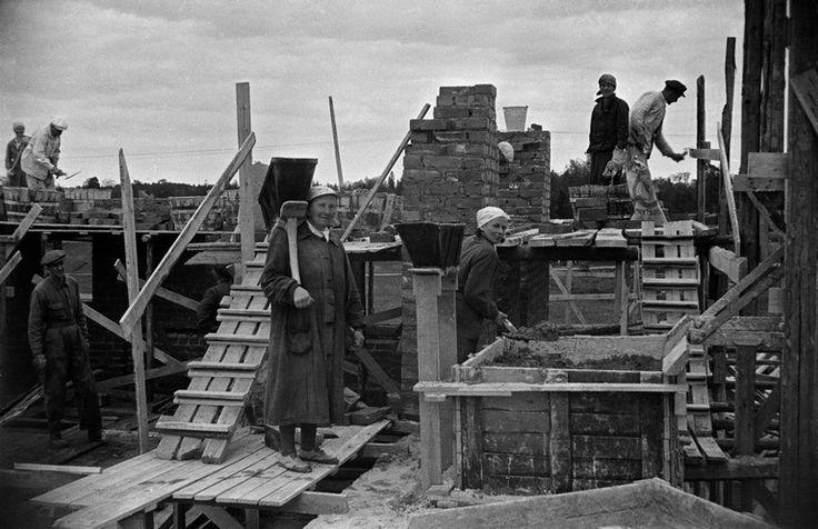 Herttoniemi, miehiä ja naisia tekemässä muuraustöitä rakennustyömaalla. n. 1954  Kuvaaj: Väinö Kannisto Lähde: HKM  (CC BY-ND 4.0).