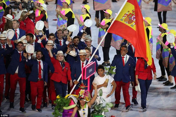 The Spanish team, wearing red and navy suits and white hats, were led through the stadium ...