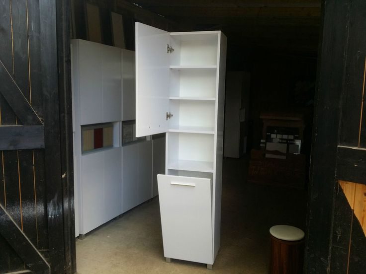 A Tall white Shelving unit with a cupboard on the bottom ...