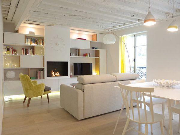 Après : La cheminée traditionnelle a été remplacée par un système de foyer urbain au bio-éthanol intégré. Et une grande bibliothèque conjuguant niches ouvertes et rangements fermés occupent toute la largeur de la pièce à vivre.