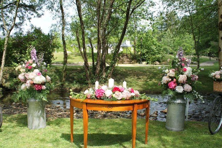 Ceremony table with unity arrangement, framed by a large floral arrangement in milk churns