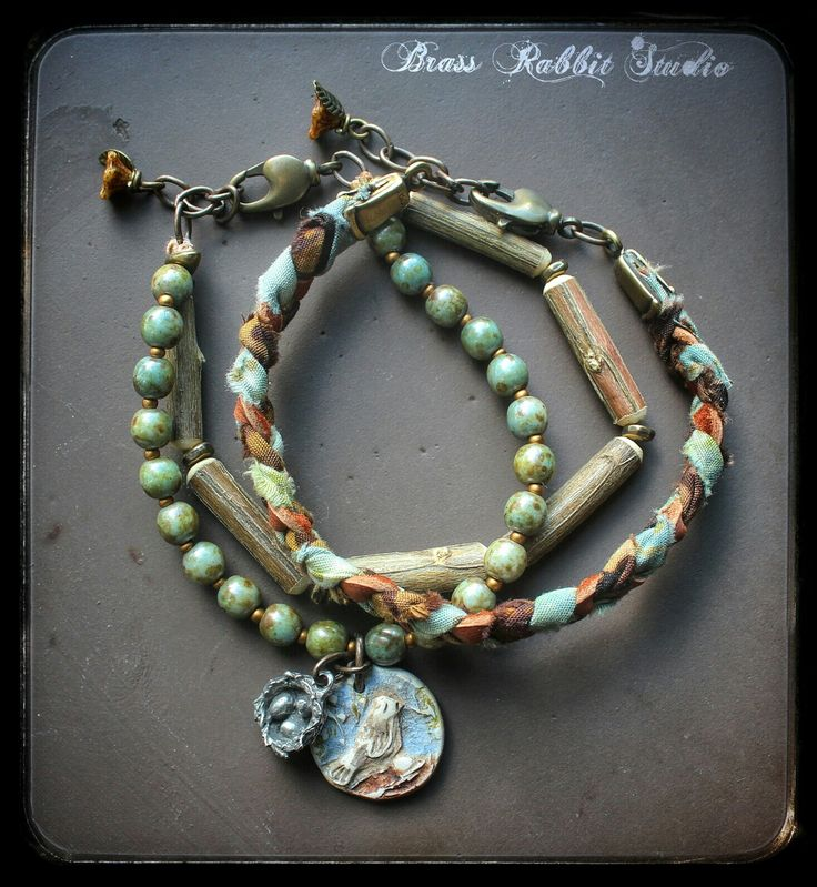 "This Earthy bracelet set with Humble beads bird charm and Green Girl bird charm comsists of two separate bracelets that when worn todether match beautifully.  The first is a single braided strand of leather and batik ribbon with a small lobster clasp, chain tail and wirewrapped czeck flower. The other is a double strand bracelet with the charms and handmade wood beads by Rich Kibbons, and picasso czech glass beads. These bracelets fit a 6""-8"" wrist.#handmade #boho #eclectic #artisan #jewelry…"