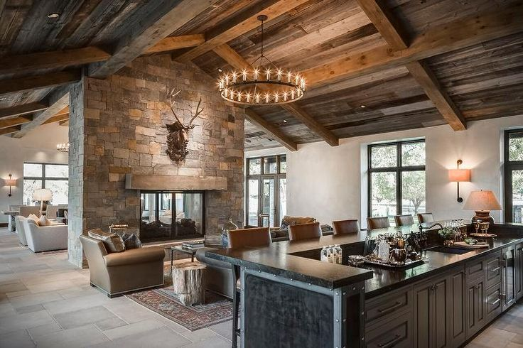 Country open plan living room boasts a double sided stone fireplace finished with glass fireplace doors and accented with a mounted gold moose head illuminated by an iron candelabra hung from a rustic plank vaulted ceiling over a seating area featuring a zinc top coffee table centered on a red and blue rug and a cognac leather club chair positioned adjacent to a tree truck end table.