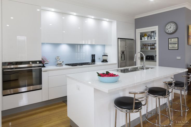 Sleek, contemporary white kitchen with pale blue glass splashback, Caesarstone benchtops