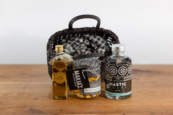 Small rattan basket with double handles in primitive brown colour containing traditional liqueur Mastic Tears 200ml, grilled white soft greek cheese (manouri) 200γρ, extra virgin olive oil seasone...