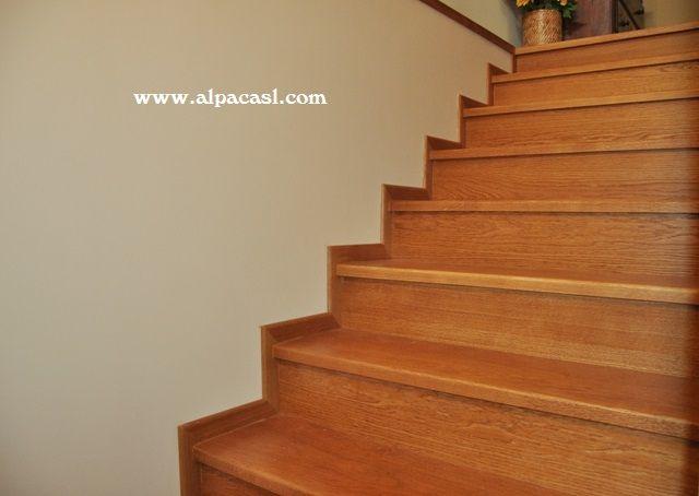 pasos de escalera en madera maciza de roble con rodapi rematando a la pared