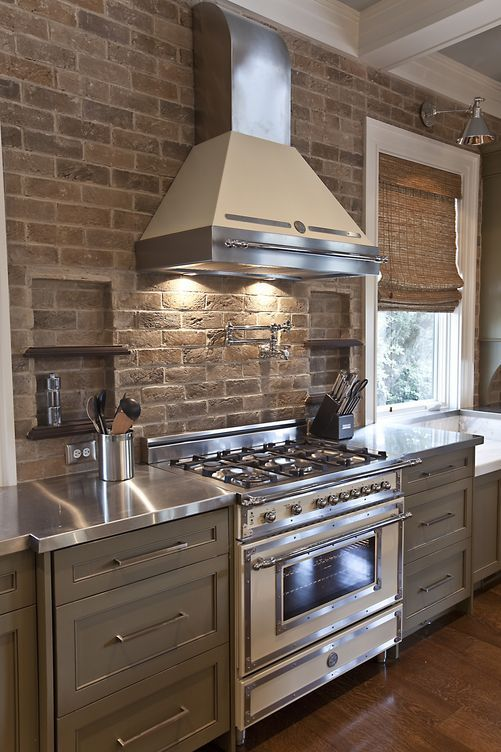 brick wall in kitchen...fabulous hood and stove...stainless steel countertops <3
