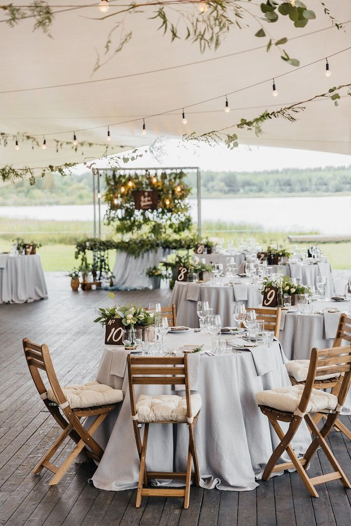 This tented wedding reception with wood flooring, gray linens and cushions on the folding chairs is perfect for an outdoor wedding