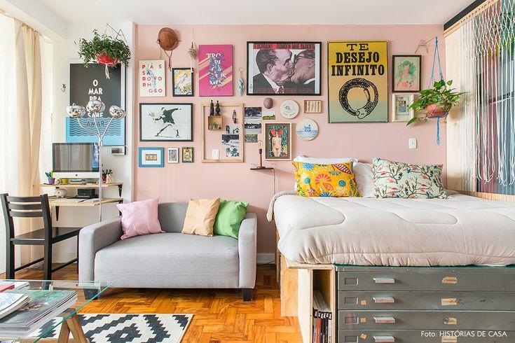 Apartamento pequeno com parede rosa e muitos quadros bem coloridos