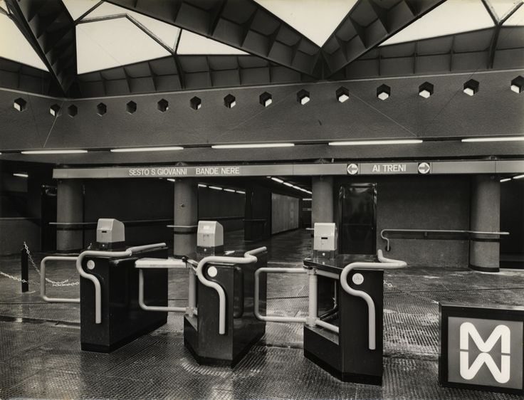 """Amendola Fiera station, line 1; hall and turnstiles, early 60's. Note the presence of the very first logo, the one with the two juxtaposed M's, soon replaced by a simpler """"MM""""."""