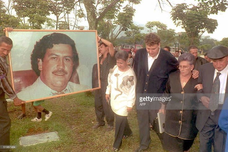 1994: Hermilda de Escobar (2nd-R), mother of Medellin drug cartel kingpin Pablo Escobar (portrait), walks with friends and relatives to Escobar's tomb to celebrate the first anniversary of his death. Escobar was killed by Colombian special forces after being discovered hiding in a house in Medellin.