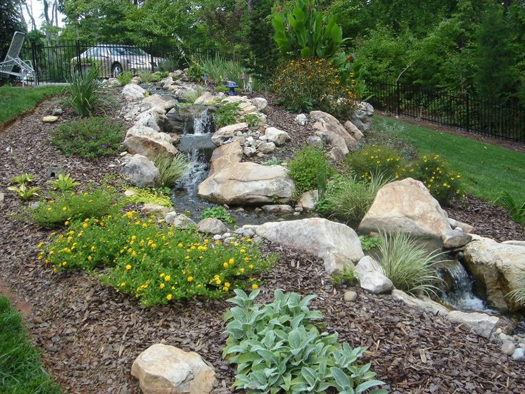 a natural looking custom built infinity waterfall and stream by living waterscapes in greensboro nc