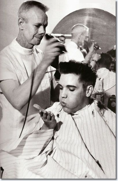 Elvis Presley blows a strand of hair from his hand, while receiving a haircut from a US Army barber, Fort Chaffee, Arkansas...