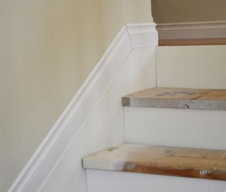 Smart!  Ad a skirt to the stairs so that you don't have to make a million angel cuts to the baseboard.