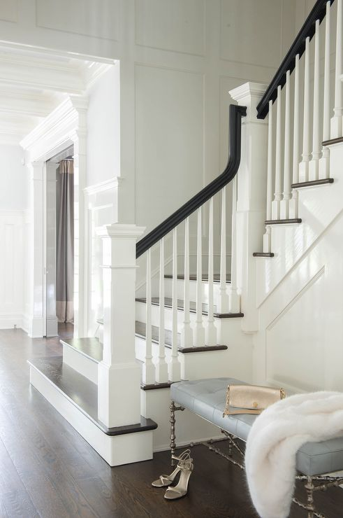 Large wainscoted walls amidst a wood panel staircase, curve elegantly while displaying black railing and column corners.