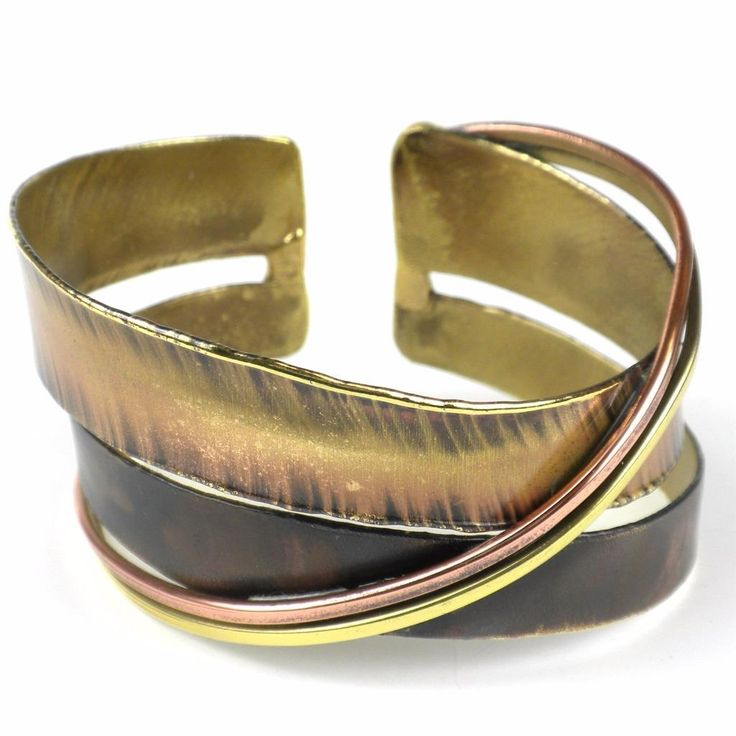 Handcrafted by South African artisans, this asymmetric darkened brass cuff is constructed from strips of brass and copper. The feathering and color on this 1.5-inch wide bracelet is achieved by applying extreme heat rather than paints or dyes.