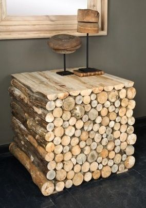 Rustic table made from stacked wood, hope it's hollow on the back or it would be a very heavy piece to move.