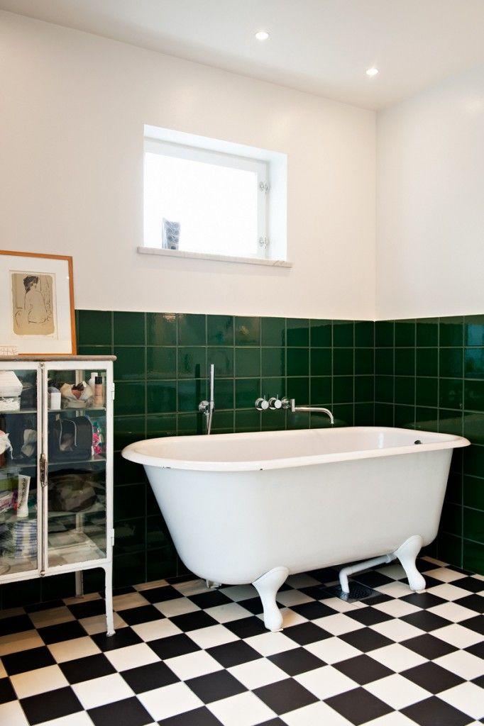 Gjutgärnsbadkar i badrum med svartvita kilnkers och grönt kakel