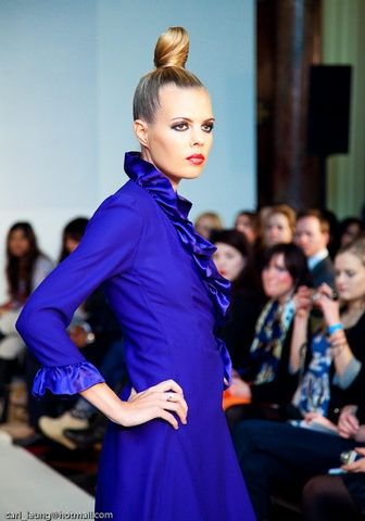 Side view of the Violet Blue Satin Crepe wrap over dress with ruffles around the neck and sleeves.