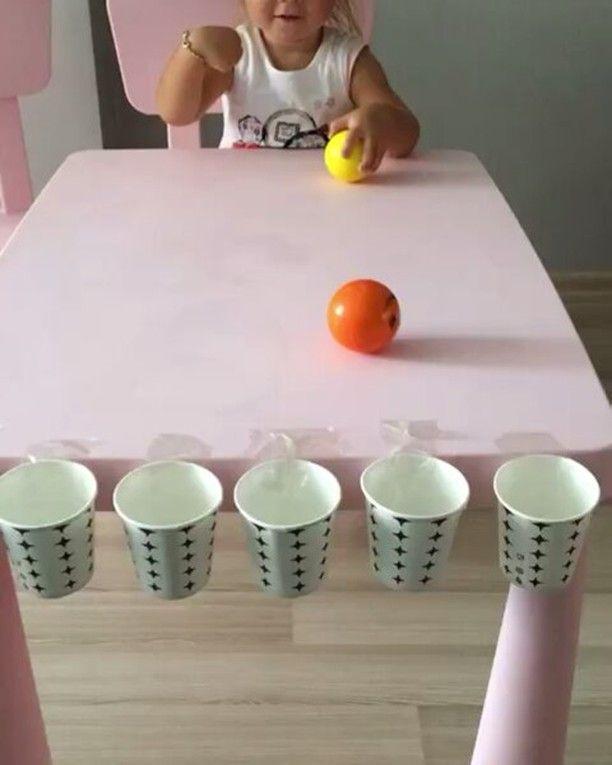 Je bevestigt aan de tafel bekers met plakband. Wanneer deze bekers aan de tafel plakken laat je het kind zitten. Als het kind zit geef je het een aantal balletjes en laat je ze de balletjes in de bekers gooien.