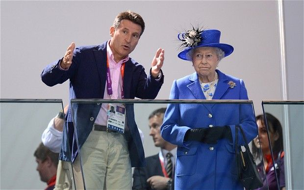 Chairman Lord Sebastian Coe (left) speaks to Queen Elizabeth II as they watch the morning session of the Swimming at the Aquatics Centre in London on day one of the London 2012 Olympics Photo: PA