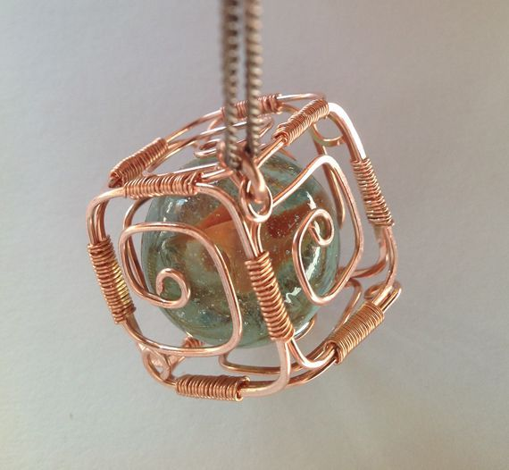 Wire-wrapped copper cube pendant with gemstone ball.