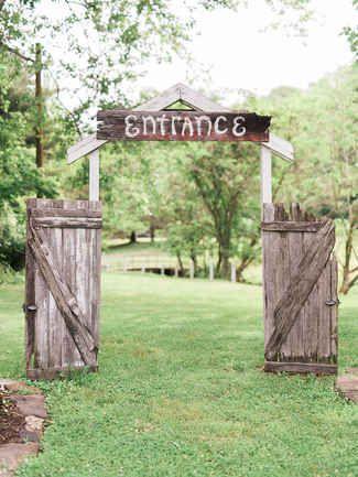 A rustic double door wooden outdoor wedding entrance
