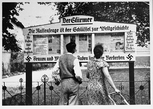 "Germans read the latest issue of ""Der Stürmer"", posted on the sidewalk in the standard 3-section display case. Nederlands Instituut voor Oorlogsdocumentatie"