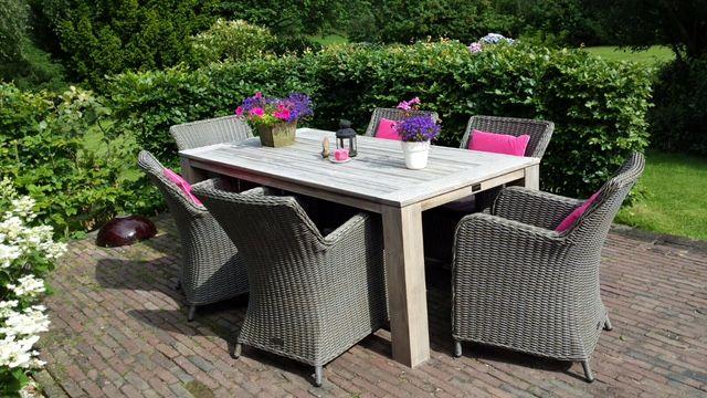 Tuinset met zes gevlochten tuinstoelen en vergrijsde teakhouten tafel