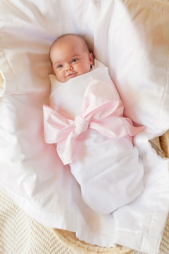 Sweet newborn baby girl tied up with a big pink bow and blue bow for boy